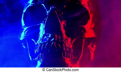 Ancient human skull head rotating in smoke close-up. Neon turquoise and red light. Spooky and sinister. Glamour, disco, halloween concept