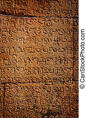 Ancient inscriptions on stone wall in Tamil language. India