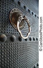 Ancient iron door with a copper doorknob