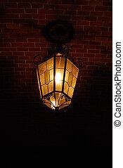 Ancient lantern on a brick wall