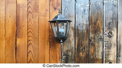 Ancient lantern on a wooden background, old lamp.
