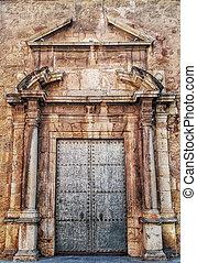 Ancient metal door with stone ornamentation