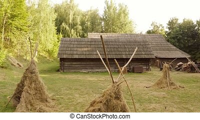 Ancient peasant cabin and hay on the yard. Old rustic wooden hut house on the field. Historical museum of life in medieval ages.