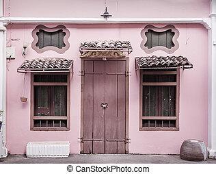 Ancient, pink building with a wooden door