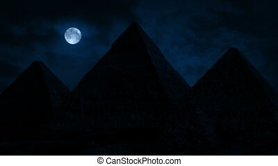 The pyramids of Giza on dramatic windy night with full moon in the sky above