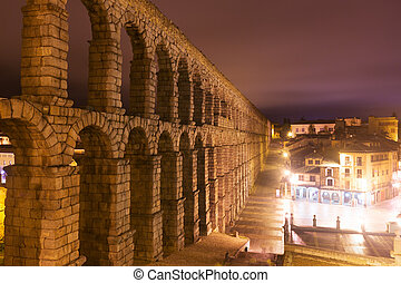 ancient roman aqueduct in night. Segovia