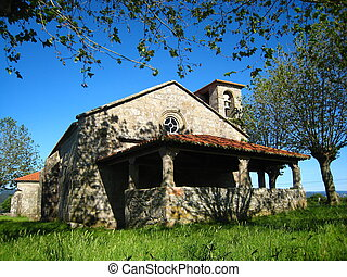 Ancient romanic church in a meadow with trees