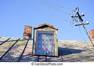 Ancient rural house tin roof attic window chimneys