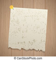 Ancient sheet of torn paper pinned with a pin. Wooden background