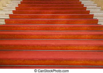 Ancient stairs with red carpet in an old building