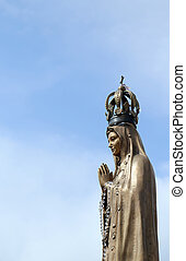 ancient statue of our Lady with clasped hands and the...