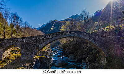 ancient stone bridge in Maggia valley in Switzerland with river and blue sky in morning light