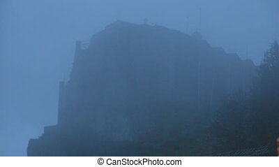 Ancient stone castle in mist, terrible atmosphere, strange old gothic building