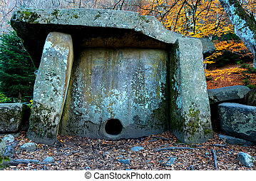 Ancient stone dolmen in the autumn forest