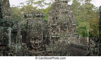 """Ancient, lichen covered faces, carved from enormous blocks of stone stand among the trees at Bayon Temple, Cambodia, with jungle sounds in the background. Video Full HD"""