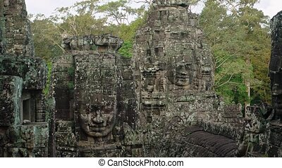 Ancient, lichen covered  faces, carved from enormous blocks of stone stand among the trees at Bayon Temple, Cambodia, with jungle sounds in the background. Video UltraHD