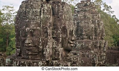 """Ancient, lichen covered sculptures of faces, carved from blocks of stone at Bayon Temple in Cambodia, with nature sounds. Video 1920x1080"""