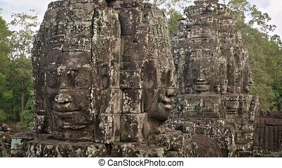 Ancient, lichen covered sculptures of faces, carved from blocks of stone at Bayon Temple in Cambodia, with nature sounds. Video 3840x2160