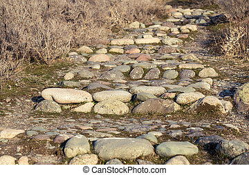 Ancient stone steps. The texture of natural stone with sprouted grass.