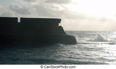Ancient stone wall and wavy sea. Acre, Israel - Slow motion...