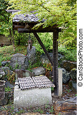 ancient stone well in japanese gard