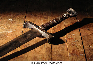 War symbol. Medieval knight sword on dirty wooden surface