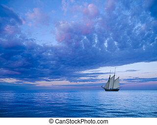 ancient two-mast schooner sailing away to the horizon