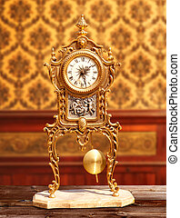 ancient vintage brass pendulum clock in classic indoor