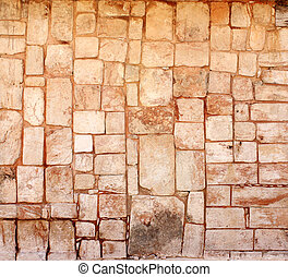Ancient wall of stone blocks in Uxmal, Mexico