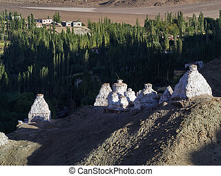 Ancient white Buddhist stupas on the ridge of a high hill in the Ladakh valley, the evening rays of the sun illuminate the stupas and long shadows stretch from the stupas along the mountain slope, the Himalayas, Northern India.