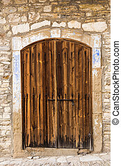 Ancient wooden door in stone castle wall.