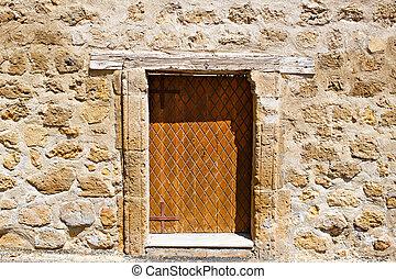 Ancient wooden door in stone wall.