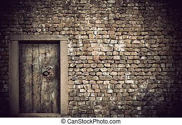 Ancient wooden door in wall built with natural rocks
