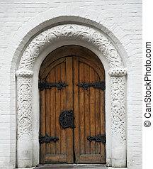 ancient wooden door with metal doorknob and hinges