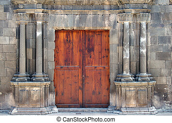 ancient wooden double doors in an old stone building with crumbling ornate fluted columns surrounding the entrance cracks and repairs in the masonry