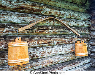 Ancient yoke with buckets. Hanging on the wall of a wooden...