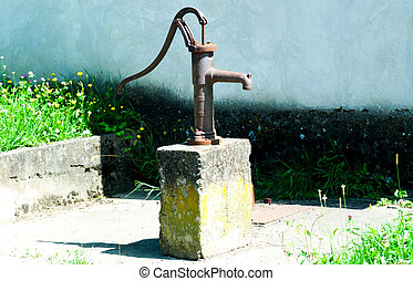and old rusty water pump on a stone block