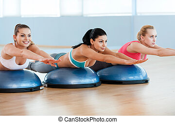 And one last stretch! Three attractive young women in sports clothing stretching together and smiling