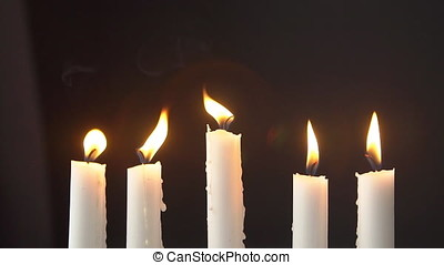 ?andles burning in the dark, yellow flame of a candle. Slow motion