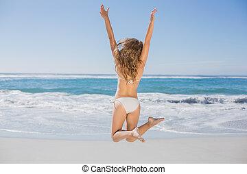 anfall, frau, in, weißer bikini, springen, auf, sandstrand