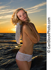 Angel girl in a sea at sunset time