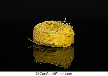 Angel hair pasta isolated on black glass