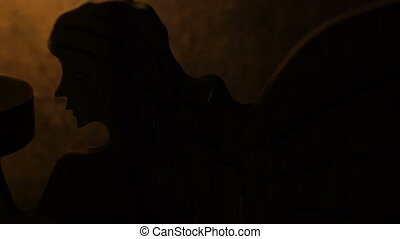 Angel lit by candle on grunge background