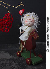 Angel of love on horseback. The red heart weighs on a dry branch. Dark background. St. Valentine's Day