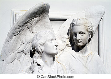 Cemetery angels made of painted over cast iron mounted on a door to a tomb. The angels have some rust.