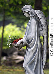 Angel Statue - A statue of an angel holding a bed of...