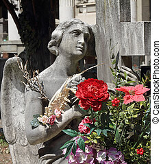 angel statue with bouquet of flowers on tomb, monumental cemetery