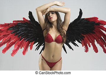 angel woman, young woman dressed in red underwear with big wings of black feathers and garnets on neutral background