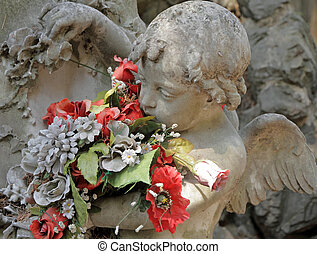 angelic sculpture with flowers , detail of beautiful tomb on monumental cemetery in Italy, Staglieno, Genova, Liguria, Europe