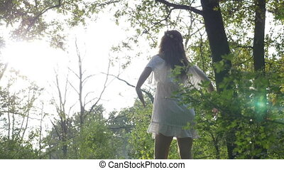 Angelic white dressed woman saluting the sun yoga relaxing in nature